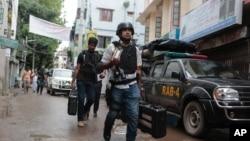 방글라데시 경찰은 26일 수도 다카 인근에서 벌어진 총격전에서 이슬람 과격분자 9 명을 사살했다고 밝힌 가운데, 상황이 종료된 후 경찰관들이 소총이 든 가방을 들고 철수하고 있다.