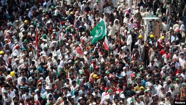 A national flag is seen amidst the supporters of Muhammad Tahirul Qadri, Sufi cleric and leader of political party Pakistan Awami Tehreek (PAT), as they gather to listen to his speech during the Revolution March in Islamabad, Aug. 16, 2014.