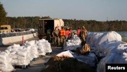 Miembros de la Guardia Nacional construyen una barrera de bolsas de arena para evitar inundaciones a causa del huracán Florence en la ruta US 501 en Carolina del Sur el miércoles, 19 de septiembre de 2018.