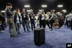 Attendees take pictures of ForwardX Robotics' CX-1 self-driving luggage during CES Unveiled at CES International Sunday, Jan. 7, 2018, in Las Vegas. (AP Photo/Jae C. Hong)