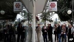 Lefkoşa'da bir bankanın önünde ATM'den para çekmek için kuyrukta bekleyen Rumlar