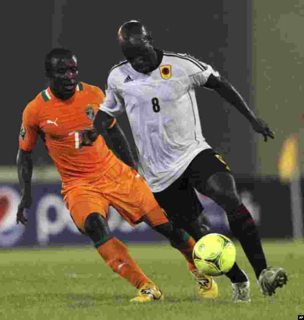 Seydou Doumbia (L) of Ivory Coast fights for the ball with Andre Macanga of Angola during their African Nations Cup soccer match in Malabo January 30, 2012.