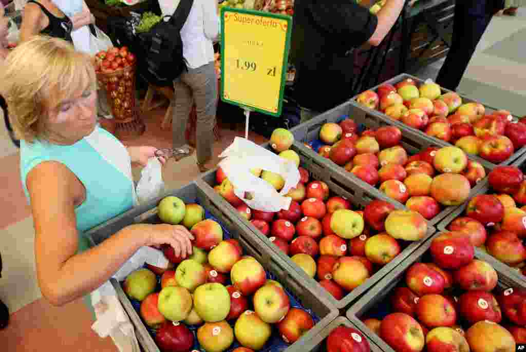 Fruit farmers marched in Warsaw to encourage Poles to eat more apples to offset the expected negative effects of a ban that Russia imposed last week on Polish fruit. In this photo, a woman is picking apples to buy at 1.99 zlotys (euro 0.47) per kilo at a supermarket in Warsaw, Poland, Aug. 6, 2014.
