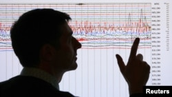Un sismólogo apunta un gráfico que registra la magnitud de un temblor.