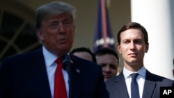 FILE - White House Senior Adviser Jared Kushner, right, listens as President Donald Trump, left, announces a revamped North American free trade deal, in the Rose Garden of the White House in Washington.