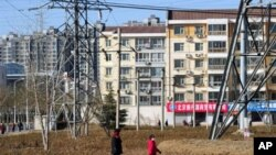 People walk past apartment blocks on the outskirts of Beijing, March 9, 2011
