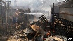 一名居民在早上試圖撲滅被砲火擊中的家園