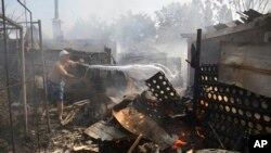 Cư dân dập tắt ngọn lửa tại ngôi nhà đang cháy ở Donetsk, ngày 7/9/2014.
