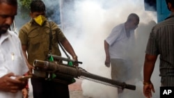 A municipal worker fumigates an area outside a train station to check the spread of mosquito-borne diseases in Mumbai, India, Sept. 3, 2016.