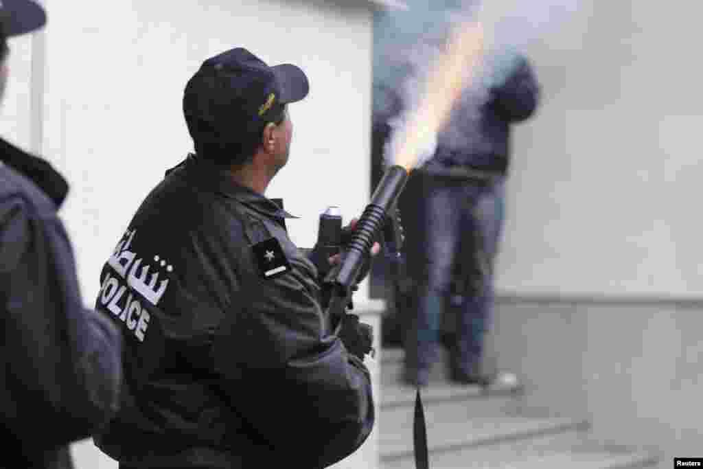 一名警官2013年2月6日在突尼斯发射催泪瓦斯来驱散一次抗议行动。