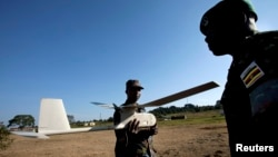 Ugandan military personnel work with a small U.S.-made drone the Ugandan military uses in Somalia to fight al-Qaida linked militants, at a demonstration and briefing at Kasenyi Military Base in Kampala, Aug. 3, 2012.