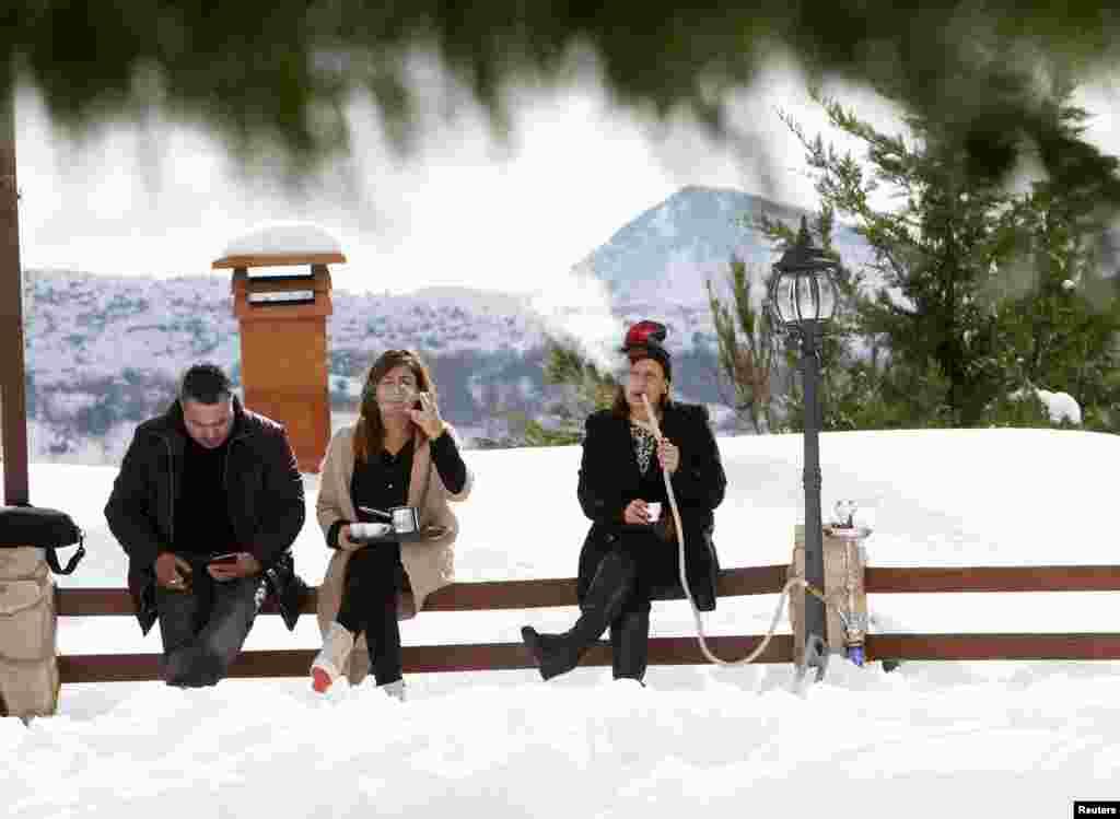 Residents smoke a hookah in snow-covered Jizeen, southern Lebanon.