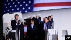 President Donald Trump, from left, greets Tony Kim, Kim Hak Song, seen in the shadow, and Kim Dong Chul, three Americans detained in North Korea for more than a year, as they arrive at Andrews Air Force Base in Md., May 10, 2018. First lady Melania Trump also greets them at right.