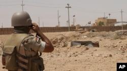 An Iraqi soldier monitors the Iraq-Syria border point, Abu Kamal, July 22, 2012.