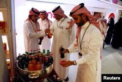 Saudi men buy soft drinks at Saudi Arabia's first commercial movie theater in Riyadh, Saudi Arabia, April 18, 2018.