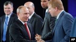 Vladimir Putin saluda a Myron Brilliant, vicepresidente ejecutivo de la Cámara de Comercio de Estados Unidos, en San Petersburgo.