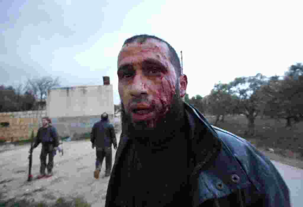 Seorang pemberontak yang terluka bergerak mundur untuk mendapatkan perawatan medis di Idlib, 8 Februari (AP).