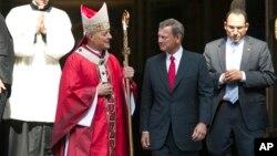 El cardenal de Washington, Dondal Wuerl, habla con el presidente de la Corte Suprema de Justicia, John Roberts, luego de la misa tradicional en la Catedral de San Mateo, que marca el inicio del período de sesiones de ese órgano.