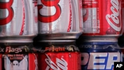 Cans of Coca-Cola and Pepsi share space on a vendor's cart Thursday, Oct. 19, 2006 in New York. The Coca-Cola Co. reported a 14 percent jump in third-quarter profit Thursday, aided by sales gains in Europe tied to World Cup soccer promotions and growth in