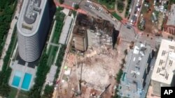 In this satellite image provided by Maxar Technologies, heavy-lift cranes are used to aid in the search and recovery operation at the partially collapsed Champlain Towers South condo building, July 3, 2021, in Surfside, Fla.