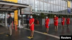Air Asia staff members stand on social distancing markings, as they wait to enter Netaji Subhas Chandra Bose International Airport (CCU), after the government allowed domestic flight services to resume, during an extended nationwide lockdown to slow the spread of the coronavirus.