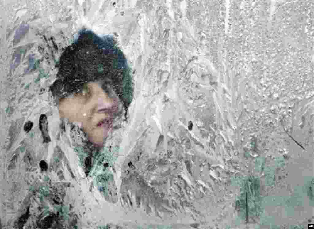 A woman looks out of a window covered in frost on a bus in Bucharest, Romania, Thursday, Feb. 2, 2012.