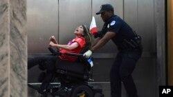 Una manifestante contra la propuesta de ley de atención médica que planean los legisladores republicanos es desalojada del Congreso de EE.UU. Sept. 25 de 2017.