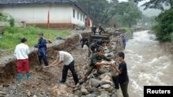 지난 2007년 8월 북한 황해북도 신평군에서 주민들이 폭우와 홍수로 부서진 하천 제방을 보수하고 있다. (자료사진)