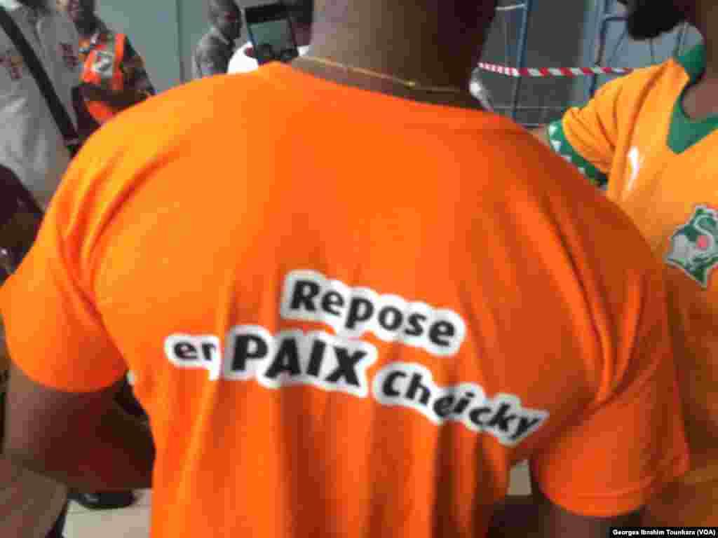 "Un Ivoirien avec un tee-shirt ""repose en paix Cheiky"", à l'aéroport d'Abidjan, le 15 juin 2017. (VOA/Georges Ibrahim Tounkara)"