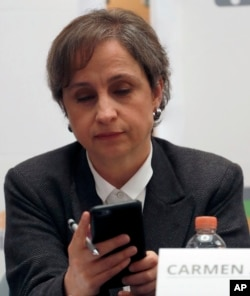 Mexican journalist Carmen Aristegui checks her phone during a press conference in Mexico City, June 19, 2017. An internet watchdog has found that Mexican journalists, lawyers and activists were targeted by Israeli-produced spyware that is sold exclusively to governments.