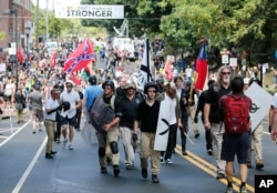 FILE - White nationalist demonstrators walk through town after their rally was declared illegal near Lee Park in Charlottesville, Va., Aug. 12, 2017.