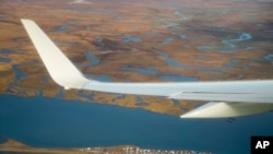 FILE - Air Force One, carrying President Barack Obama, flies over the island village of Kivalina, an Alaska Native community of 400 people already receding into the ocean as a result of rising sea levels, on its way to Ralph Wien Memorial Airport, Sept. 2, 2015, in Kotzebue, Alaska.