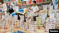 A Thai vendor weighs a bag of rice at a market in central Bangkok, July 26, 2013.