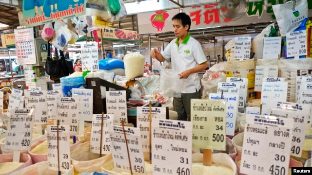 FILE - A Thai vendor weighs a bag of rice at a market in central Bangkok.
