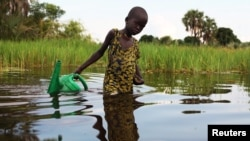 FILE - A girl prepares to collect water in a plastic can in South Sudan, Aug. 19, 2018.