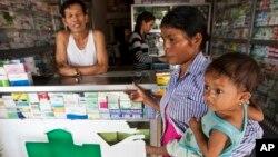 Seorang pemilik toko berbicara dengan perempuan yang mencari obat bagi anaknya yang terjangkit malaria di Pailin, Kamboja (foto: ilustrasi).