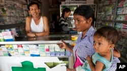 In this Aug. 26, 2009 file photo, a merchant speaks with a woman holding her ill child at a pharmacy in Pailin, Cambodia.