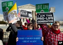 FILE - In this Jan. 18, 2019, file photo, anti-abortion activists protest outside of the U.S. Supreme Court, during the March for Life in Washington.