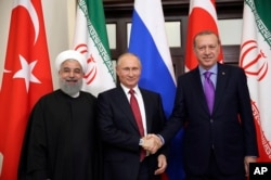 FILE - Turkey's President Recep Tayyip Erdogan, right, Russia's President Vladimir Putin, center, and Iran's President Hassan Rouhani pose for the media members in Sochi, Russia, Nov. 22. 2017.