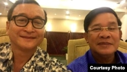 A widely shared photo on Cambodian social media, Cambodian opposition leader Sam Rainsy and Prime Minister Hun Sen take a selfie to affirm their 'culture of dialogue' at a dinner between the two families at Cambodiana Hotel in Phnom Penh, Sunday, July 12, 2015. (Courtesy of Sam Rainsy)