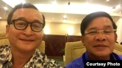 A widely shared photo on Cambodian social media, Cambodian opposition leader Sam Rainsy and Prime Minister Hun Sen take a selfie to affirm their culture of dialogue at a dinner between the two families at Cambodiana Hotel in Phnom Penh, Sunday, July 12, 2