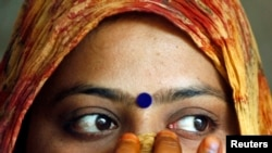 FILE - A woman wearing a bindi waits after casting her vote at a polling station in the old quarters of Delhi.