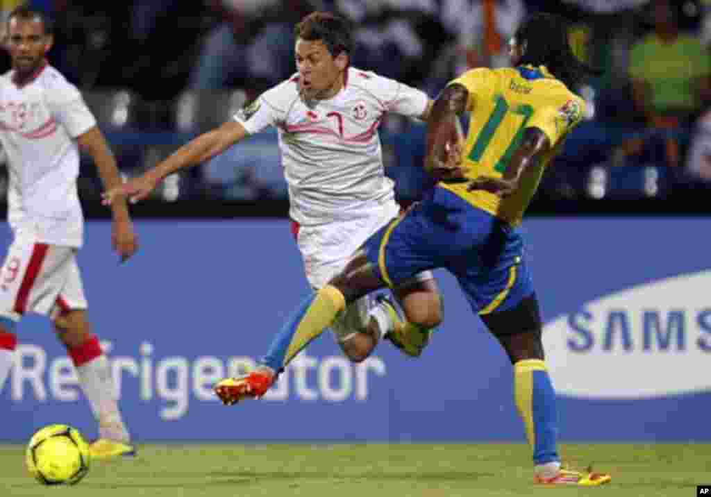 Tunisia's Youssef Msakni (L) challenges Moise Brou Apanga of Gabon during their African Cup of Nations Group C soccer match at Franceville stadium in Gabon January 31, 2012.