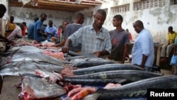 FILE - Somali traders prepare sword fish at the Hamarweyne market in southern Mogadishu, Aug. 16, 2010.