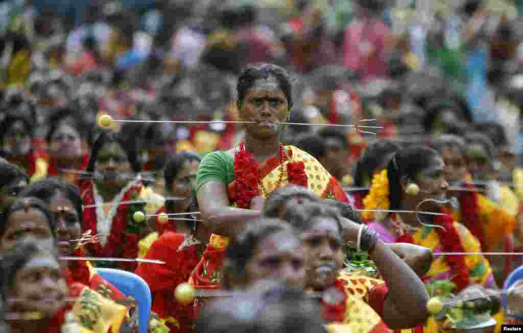 Devotees with their mouths pierced with tridents participate in a ritual to worship the Hindu goddess Durga during Aadi festival celebrations in the southern Indian city of Chennai.