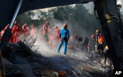 Tim SAR terus melakukan pencarian korban di antara puing-puing bangunan yang runtuh di Izmir, Turki, 2 November 2020.