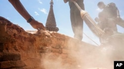 Using brooms and bare hands, soldiers and residents clean up earthquake-damaged Htilominlo Pagoda in Bagan, Myanmar, Aug. 25, 2016.