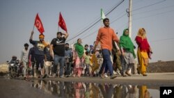 A group of protesters shout slogans as they arrive to join farmers demanding to abolish new farming laws they say will result in exploitation by corporations, eventually rendering them landless, at the Delhi-Haryana state border, India, Dec. 1, 2020.