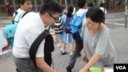 有中學生經過陳澤滔擺設的街站,簽名支持興建寵物公園。(美國之音湯惠芸拍攝)