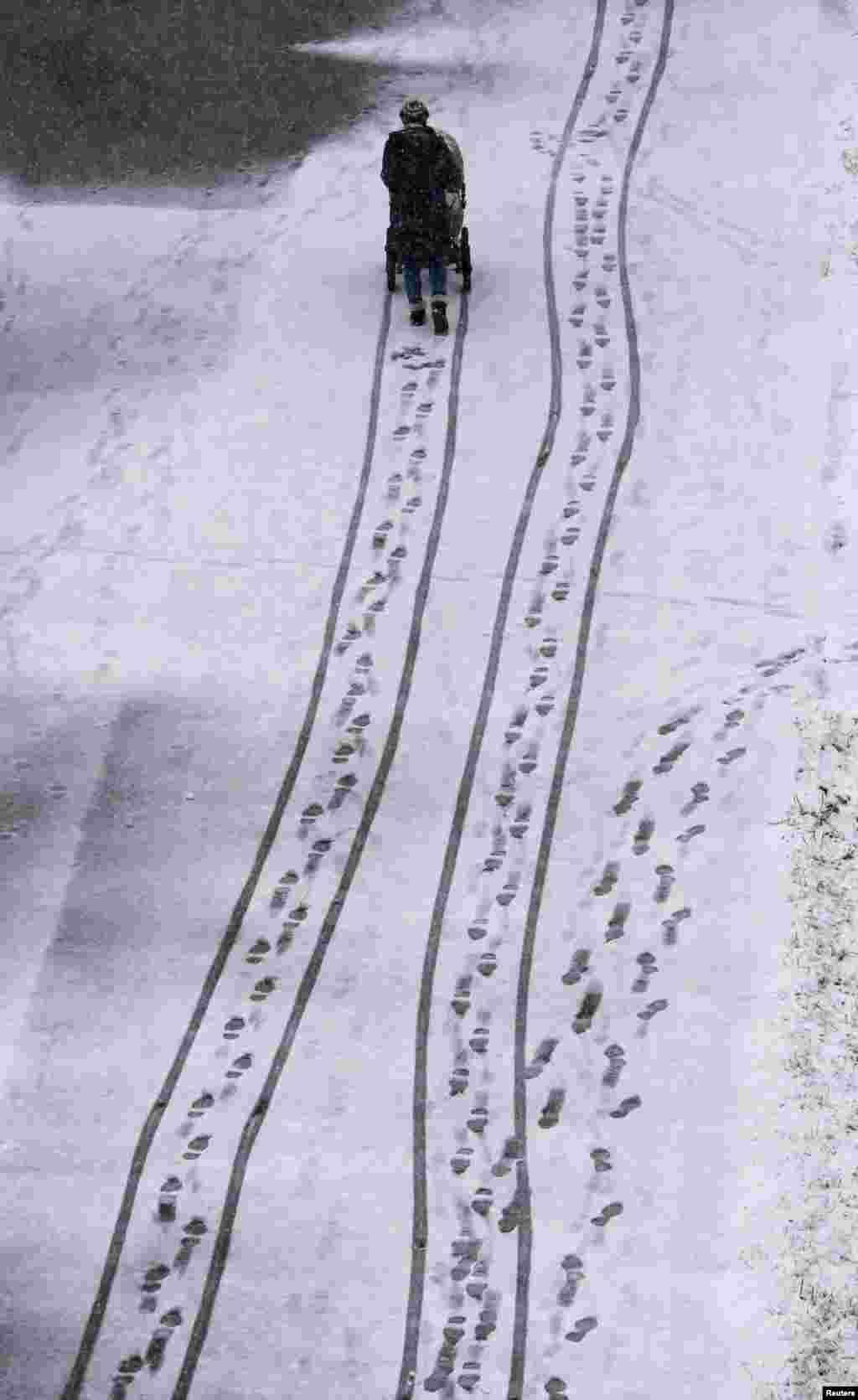 Seorang perempuan mendorong kereta bayi pada saat hujan salju lebat di kota Krasnoyarsk, Siberia, Rusia.